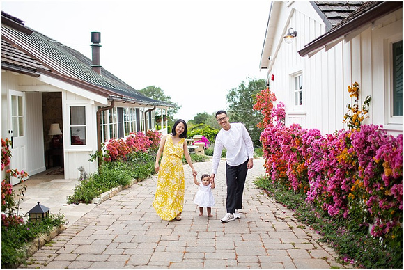 A family session wearing white and yellow in a flower garden on a bright day